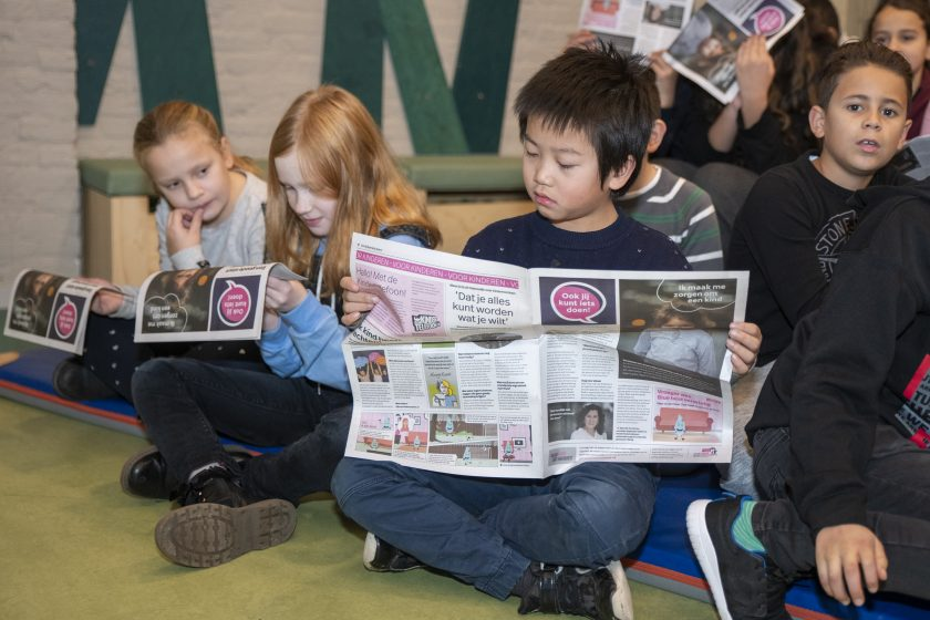 kind leest krant over kindermishandeling